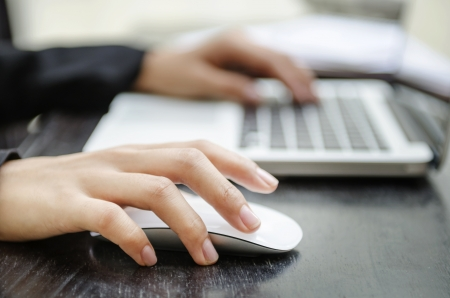 mouse click: Woman hand on mouse and other one on keyboard