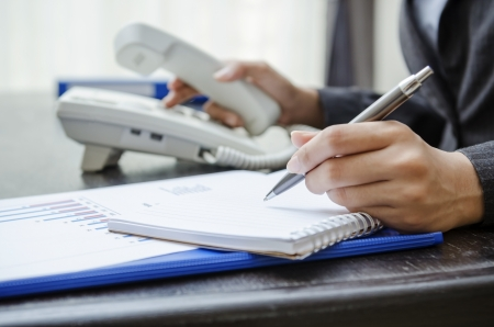 Businesswoman dialing and writing on note book