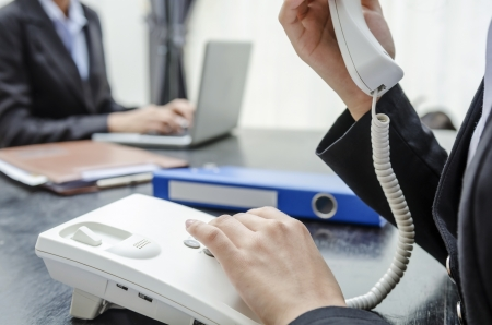 Business person making a call and another working on PC Stock Photo - 21958316