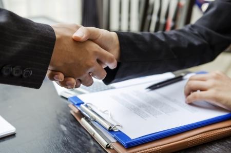 manos juntas: Empresaria mano temblorosa para un acuerdo Foto de archivo