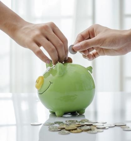 Macro of adult hands saving US coins Standard-Bild