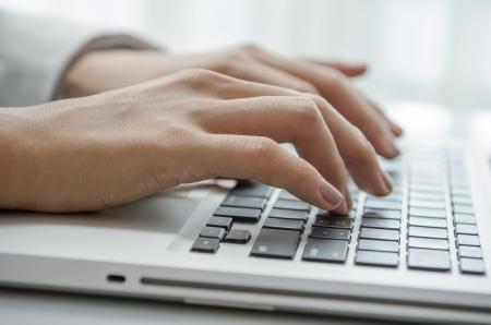 Closeup of female hand typing PC photo