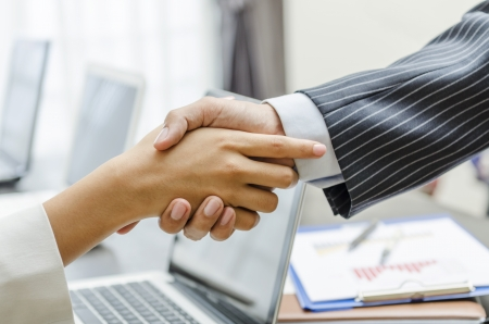 Businessman and businesswoman handshaking in office photo