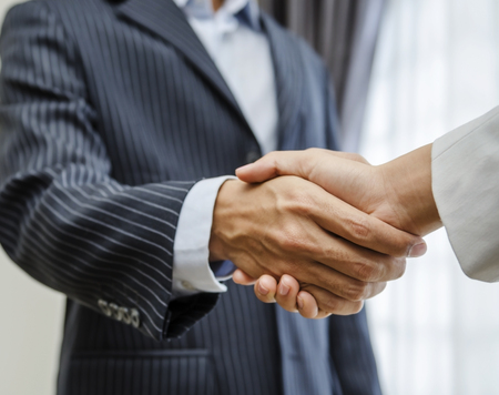 asian business people: Businessman handshaking with businesswoman in office