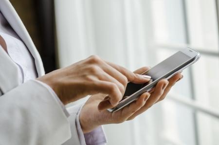 Closeup of woman hand touching smart phone Standard-Bild