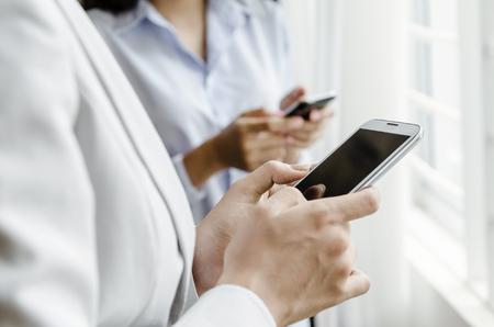 smart phone: Businesswomen using smart phone in front of window