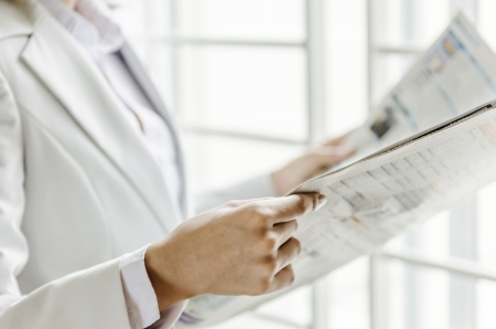 Closeup woman hand holding newspaper