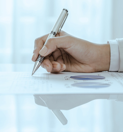 hand holding pen: Closeup of woman hand holding pen on document Stock Photo