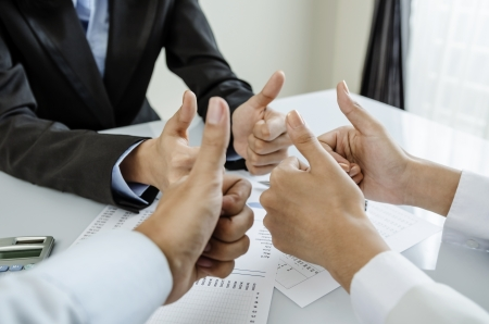 Group of business people show thumb up