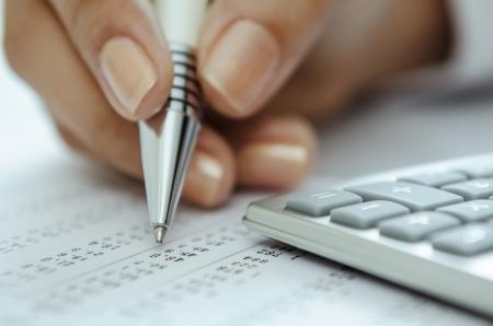 hoja de calculo: Empresaria mano que sostiene la pluma en la hoja de c�lculo