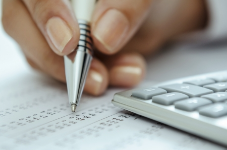 Businesswoman hand holding pen on spreadsheet