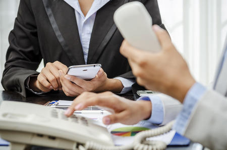 Business people using smart phone and telephone photo