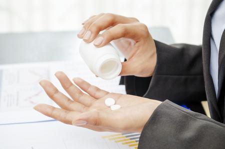 painkillers: Businesswoman taking painkiller in office