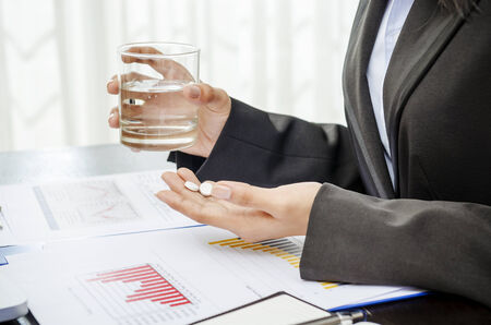 pills in hand: Business person holding medicine and glass of water