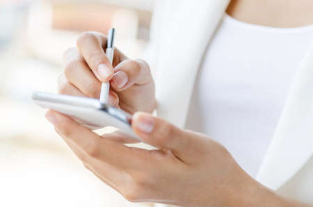 Closeup of a woman hands using tablet with stylus pen photo