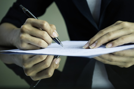 closeup of woman hands signing a contract
