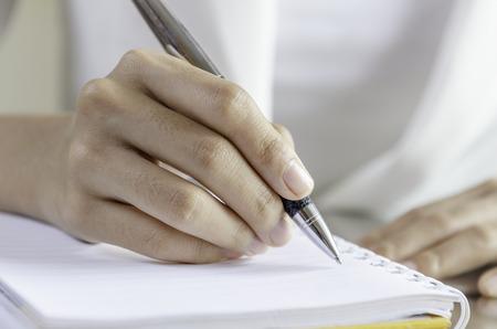 closeup of woman hands writing on a notebook Standard-Bild