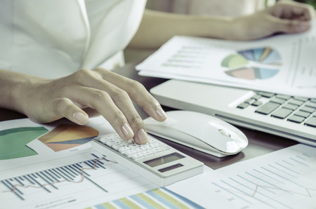 Woman using a calculator in office