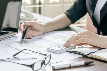 calculator: woman working on business plan with a calculator