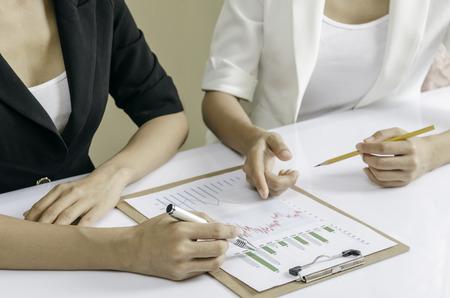 revisando documentos: personas discutiendo gráfico financiera en una carpeta