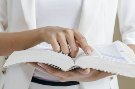 business book: closeup of womans hands skimming through a dictionary