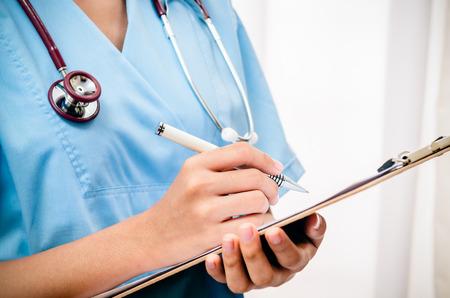 nurse uniform: surgeon taking records about patient after surgery