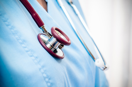 close up of doctors blue uniform and stethoscope