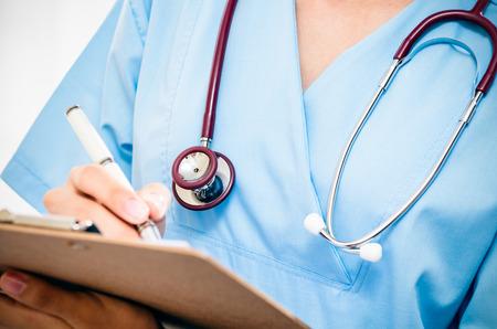 salud: cirujano teniendo registros acerca paciente después de la cirugía Foto de archivo