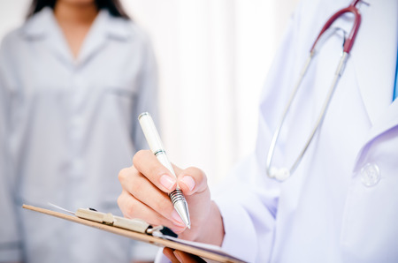 examine: doctor writing patients record after examine health