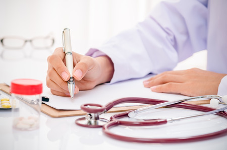 medicine and science: doctor writing record on folder on desk in office