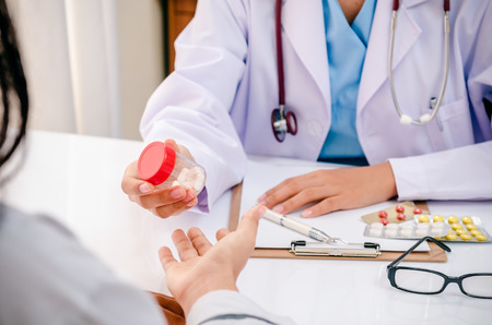 doctor holding pills: close up of doctor giving medicine to patient Stock Photo