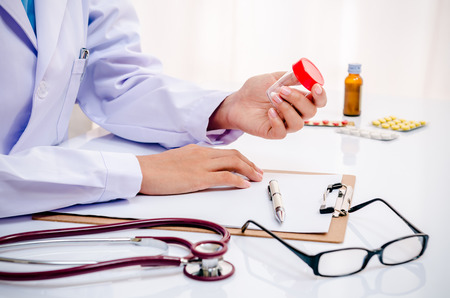 doctor checking medicine and recording document in office