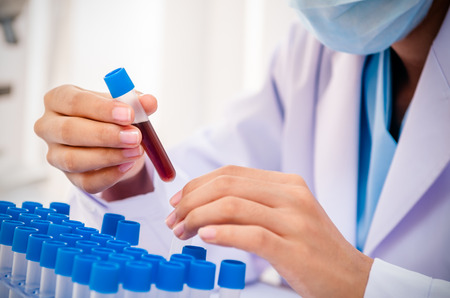 evaluating: close up of scientist examining chemical tubs in lab Stock Photo