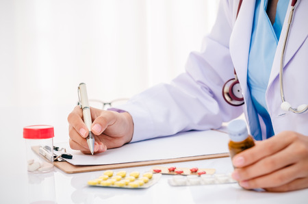 close up of doctor writing record on folder while holding medicine in office