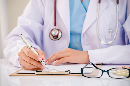 doctor writing record on folder while holding medicine in office Standard-Bild