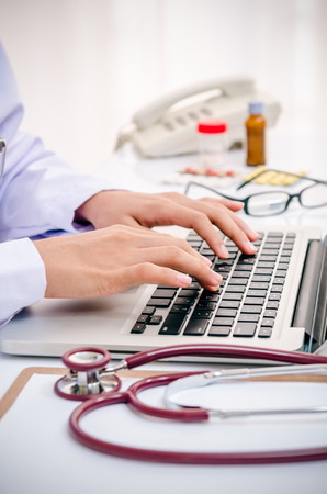 close up of doctor typing information on the computer in office Banco de Imagens - 41452369