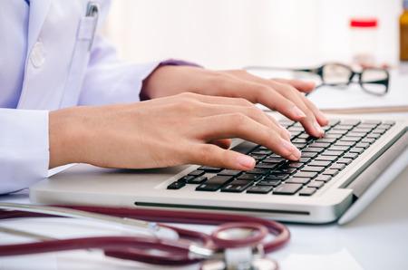 médecin des informations tapant sur l'ordinateur dans le bureau Banque d'images