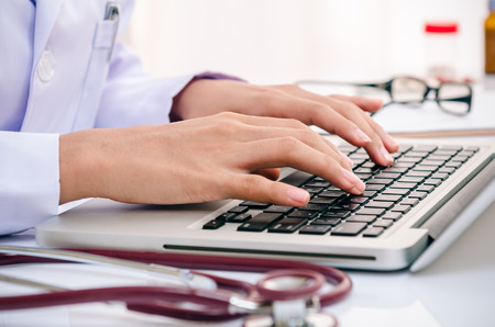mecanografía: médico escribir la información en el ordenador en la oficina