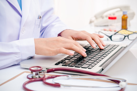 doctor typing information on the computer in office Standard-Bild