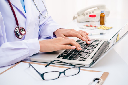 background check: doctor typing information on the computer in office Stock Photo