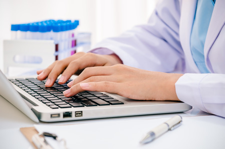 close up of scientist recording chemical tubs onto computer 스톡 콘텐츠