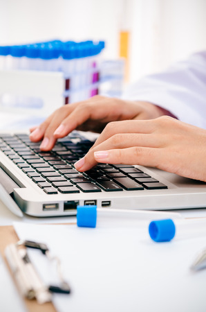 health woman: portrait of scientist examining and recording chemical tubs onto computer Stock Photo
