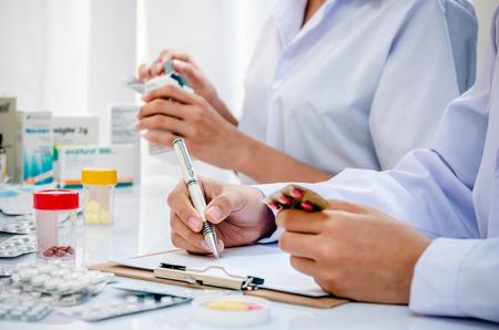 medicine box: two pharmacists preparing prescription and medicine box