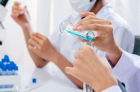 formulate: laboratory workers experimenting different liquid in flask containers