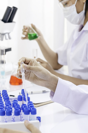 formulate: physicians examining and testing different liquids in tubes