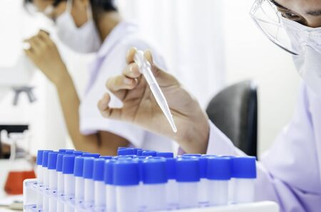 formulate: researcher working on liquid test in tube