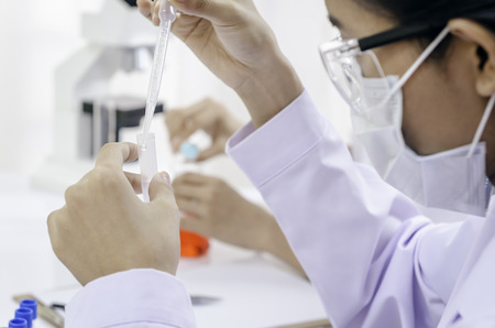 formulate: medical doctor examining liquid in tube carefully Stock Photo