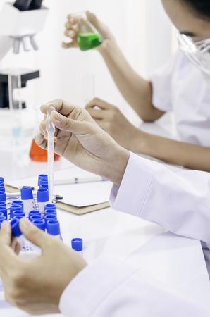 liquids: chemists examining and testing different liquids in tubes