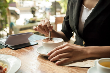 breakfast room: close up of woman stirring her coffee