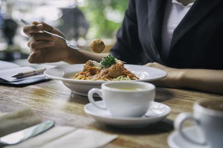 concentrarsi sulla donna mangiare gli spaghetti con la tazza di tè